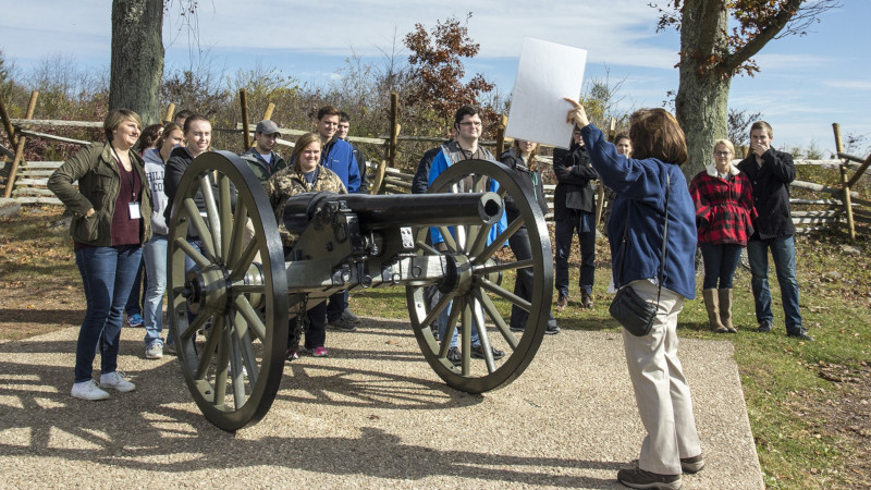 Students at Gettysburg listening to tour guide next to a cannon.